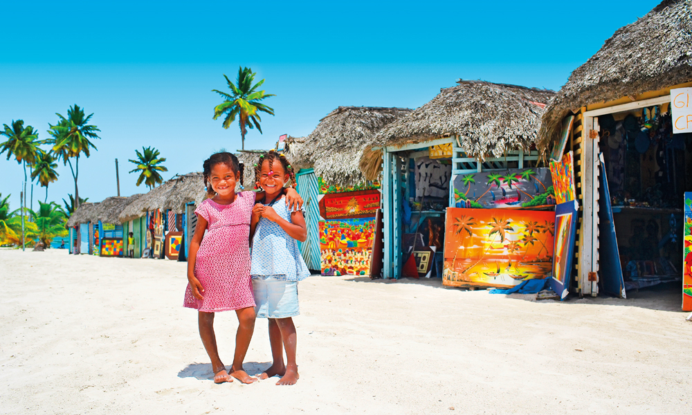 Mens fransktalende Haiti ligger vest på Hispanola, er det spansk som gjelder i Den dominikanske republikk. Lokalbefolkningen er godt vant til turisme, og smilene sitter løst når unge strandløvinner ønsker velkommen til stranda. Foto: Apollo