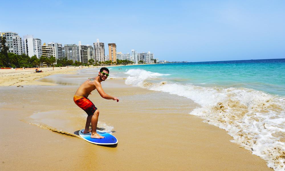 Surferen Gabriel Enriques trener på brettet sitt i småbølgene på Ocean Parque-stranda og ønsker nordmenn hjertelig velkommen – uten sko. Foto: Torild Moland