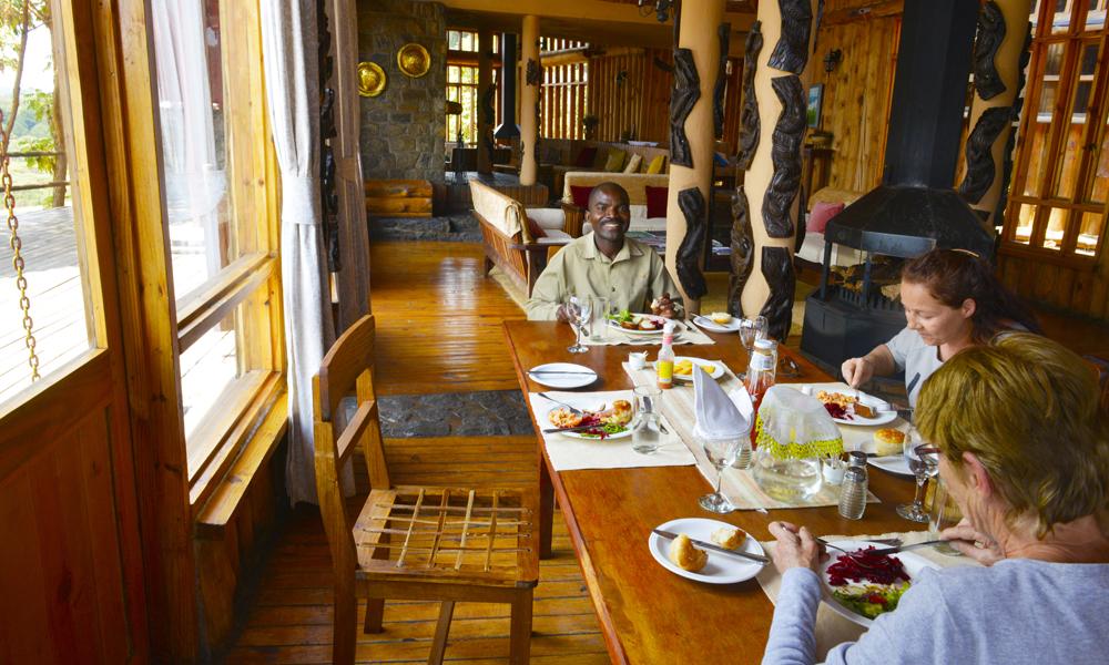 Med bare tre gjester på hele Chelinda Lodge blir det naturlig å sitte sammen til bords ved måltidene. Og på hedersplassen ved enden av bordet sitter hovedguide Whyte Mhone. Foto: Gjermund Glesnes