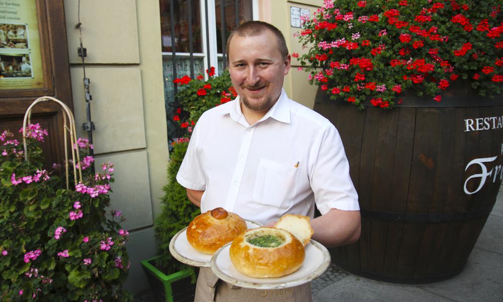 Tomasz Wyskoczyl (28) serverer tradisjonell zurek i brød på restaurant Pod Freda midr på den historiske handelsplassen. Foto: Runar Larsen