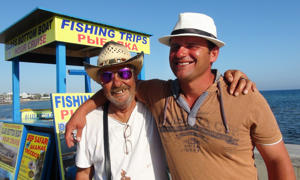 Fisketurer, dagscruise, jeepsafari – det er nok å gjøre. Andy Pearson (63) og Michail Todorov (57) anbefaler tur med fiskebåt fra havna i Pafos. Kanskje ikke så rart – de selger dem. Foto: Torild Moland