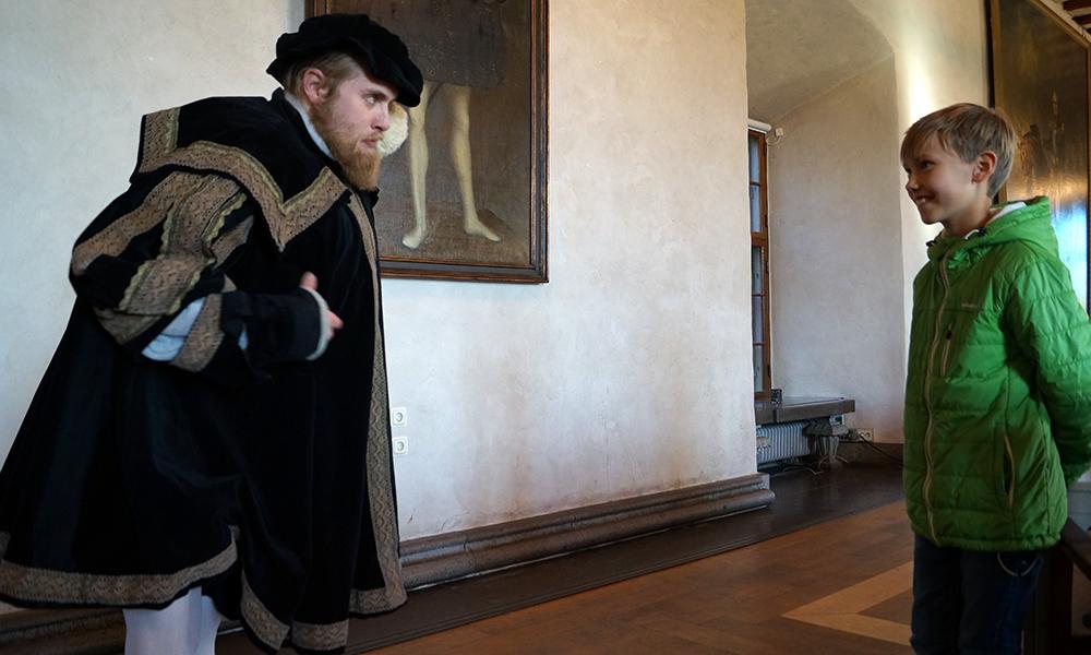 Kong Gustav Vasa gir Oskar Nicolai (8) en leksjon hvordan en bør kle seg og se ut for å være en skikkelig konge. Man skulle være tjukk, skjeggete og gå med hvite strømpebukser. Foto: Trude Grande Fjellbirkeland