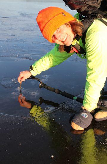 Torill Lundh sjekker isens tykkelse med en medbragt måler, og forsikrer gjengen om at den er trygg. Foto: Ida Anett Danielsen