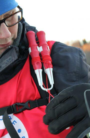 Edgar Barsjø viser frem isbroddene, som sammen med kasteline er noe av det viktigste utstyret å ha med på isen. Foto: Ida Anett Danielsen