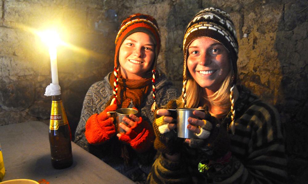 Mia K. Kalleberg og Ingrid får i seg varmen i en hytte de låner langs veien for å søke ly for regnet. Foto: Ingrid Holtan Søbstad