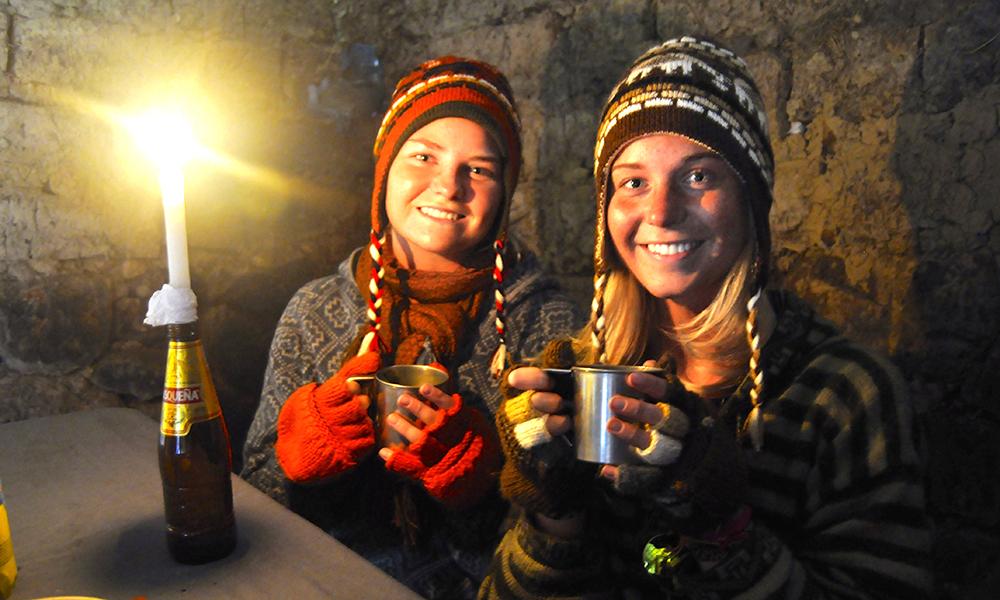 Mia Kalleberg og Ingrid (t.h) får i seg varmen i en lånt hytte for å søke ly for regnet. Foto: Ingrid Holtan Søbstad