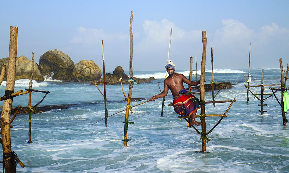 De ikoniske styltefiskerne er blitt en levende turistattraksjon. Jagath Kumara er spesielt fornøyd med at han har vært avbildet i Lonely Planets guide til Sri Lanka, og innrømmer glatt at han er mer fotomodell enn fisker. Foto: Runar Larsen