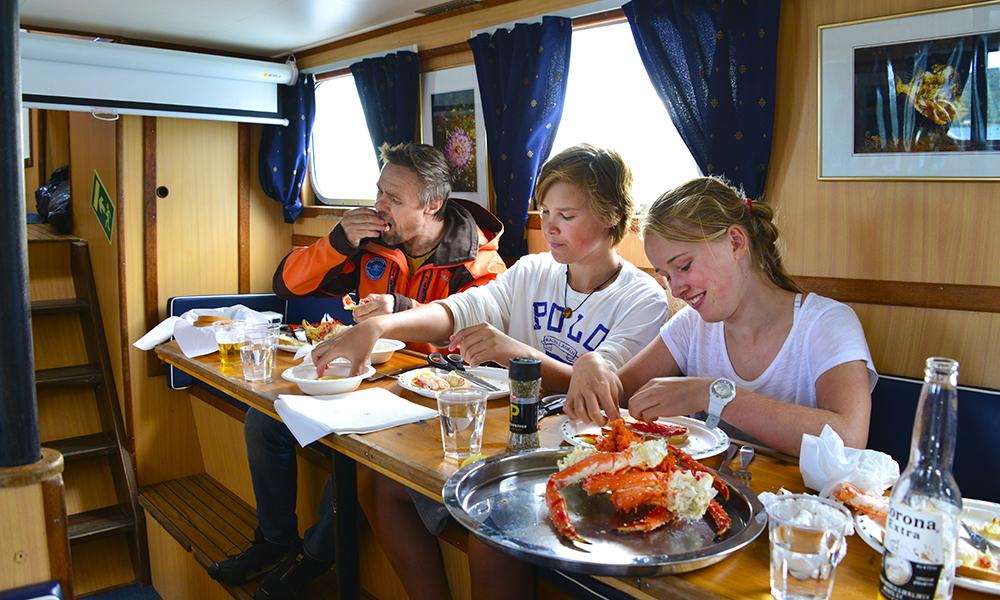 Jacob Krogsrud (14), Ronny Frimann (56) og Emilie Krogsrud (12) nyter dagens fangst under dekk. Foto: Torild Moland