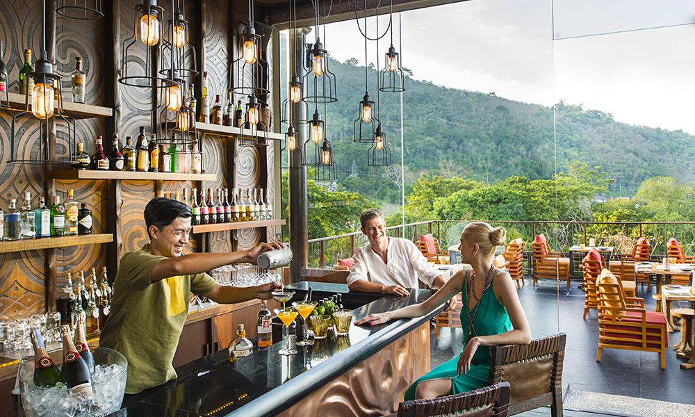 Veggene i hotellets bar og restaurant består av tre og jordlige elementer. Et perfekt sted for å drikke friske drinker og se sola gå ned. Foto: Keemala