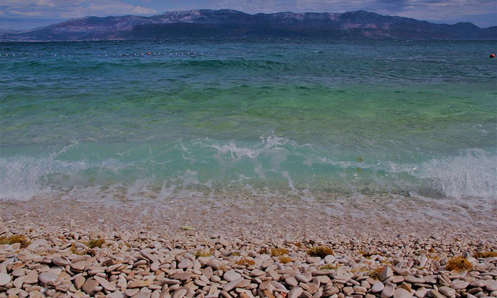 Typisk Kroatia – rullesteinstrand, turkist vann og fjell i sikte. Foto: Kari Wallem Bøe