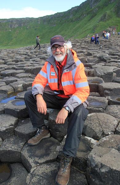 Philip Robinson (58) jobber som vakt ved Giants Causeway, og forklarer gjerne historien og mytene bak steinformasjonene. Foto: Runar Larsen