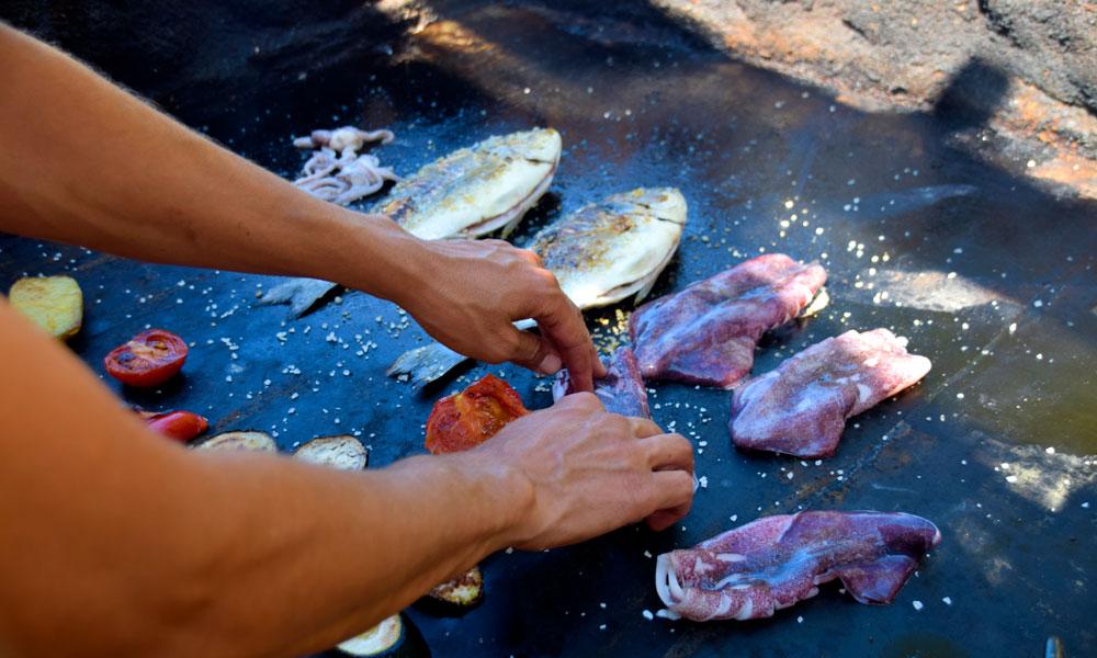 """La kokken på den lille strandrestauranten på Utopia grille fersk """"dorada"""" og """"calamari"""" til deg, mens du tar et svalkende bad. Foto: Mari Bareksten"""