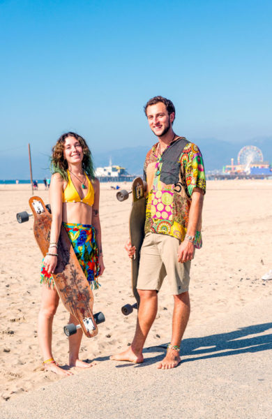 Mann og dame med longboard poserer for kamera.