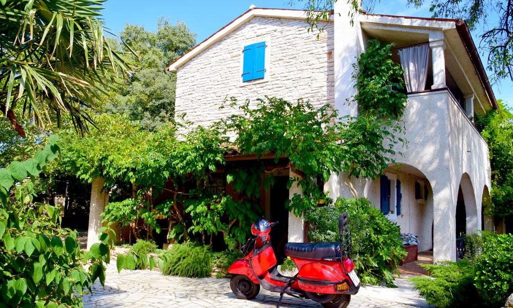 Skabe farmhouse i grønne omgivelser og en rød scooter.