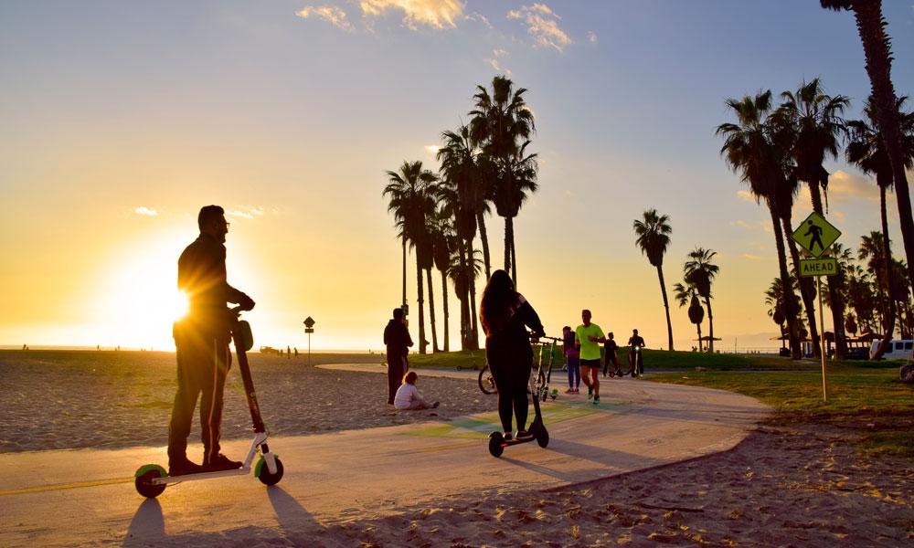 Folk på sparkesykkel i solnedgang.