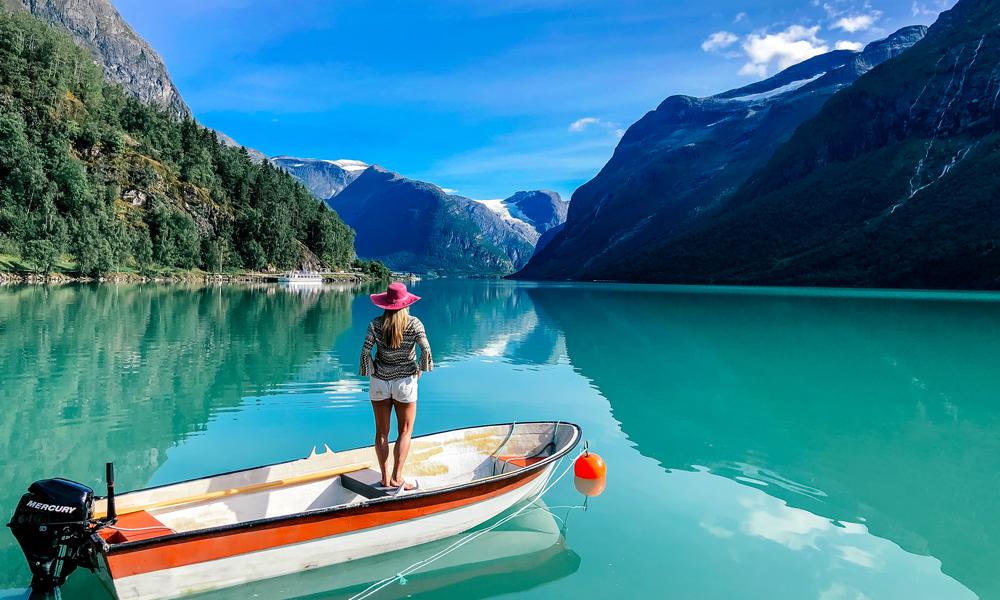 Dame står i båt og ser utover Lovatnet
