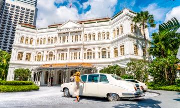 Nyvasket hvit vintage Daimler Limousine står parkert utenfor det herskapelige hotellet Singapore Raffles.